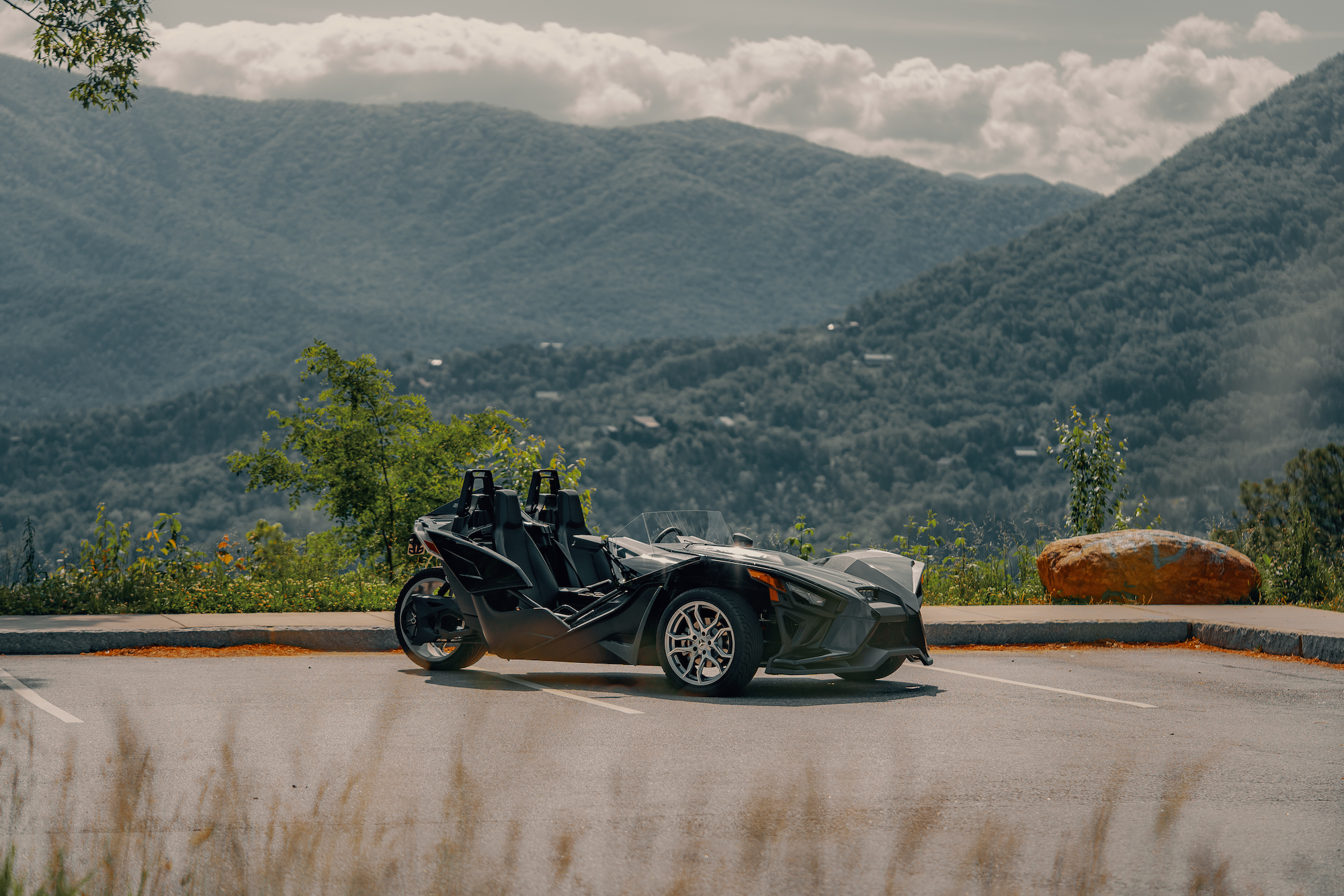 Polaris Slingshot parked with mountains in the background - Polaris Slingshots are available as rentals at the Mountain Mile Mall at Mountain Mile Adventures in Pigeon Forge, Tennessee