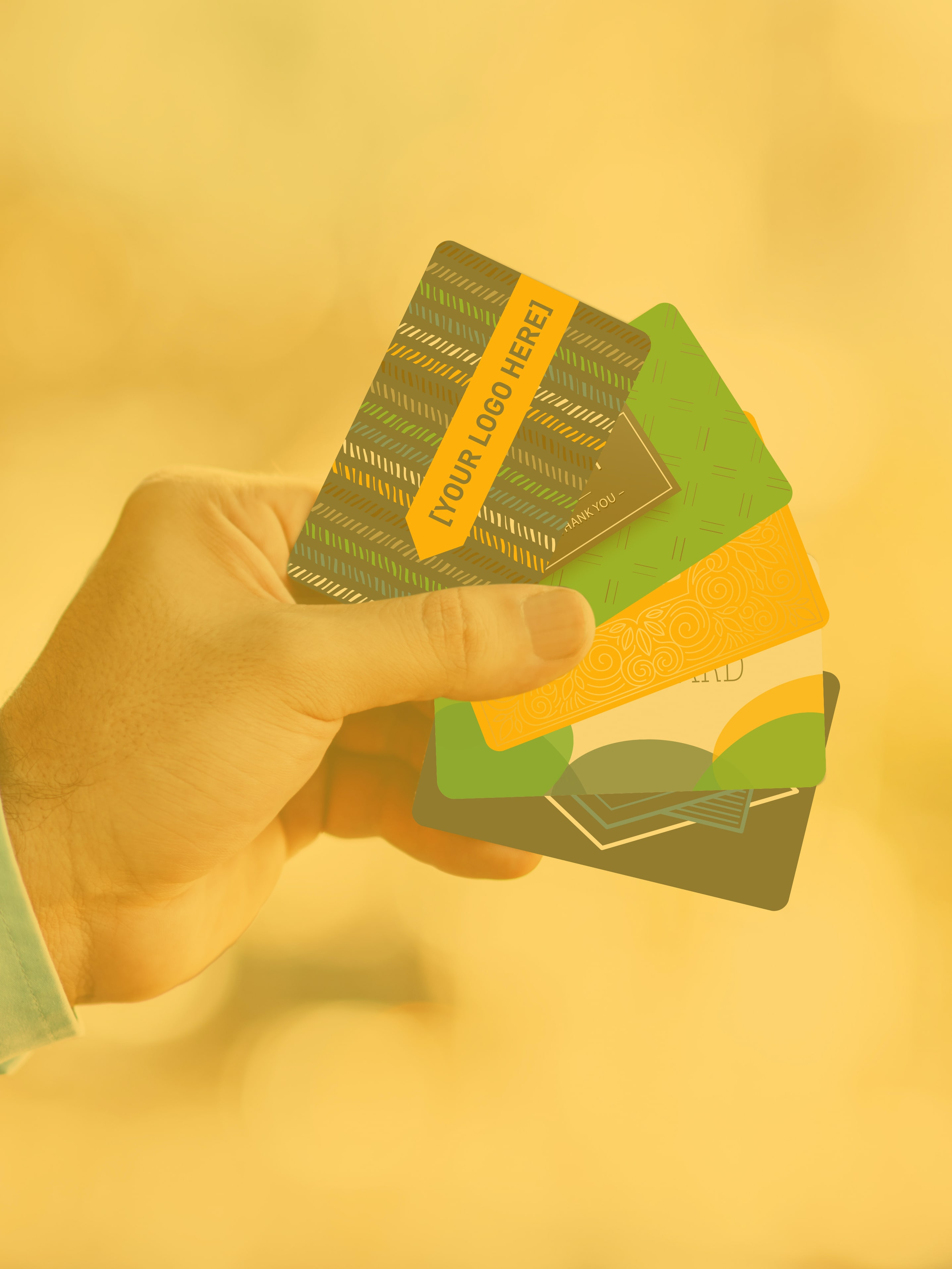 A man's left hand fans out five generic gift cards that represent custom designs for your business' gift card program.