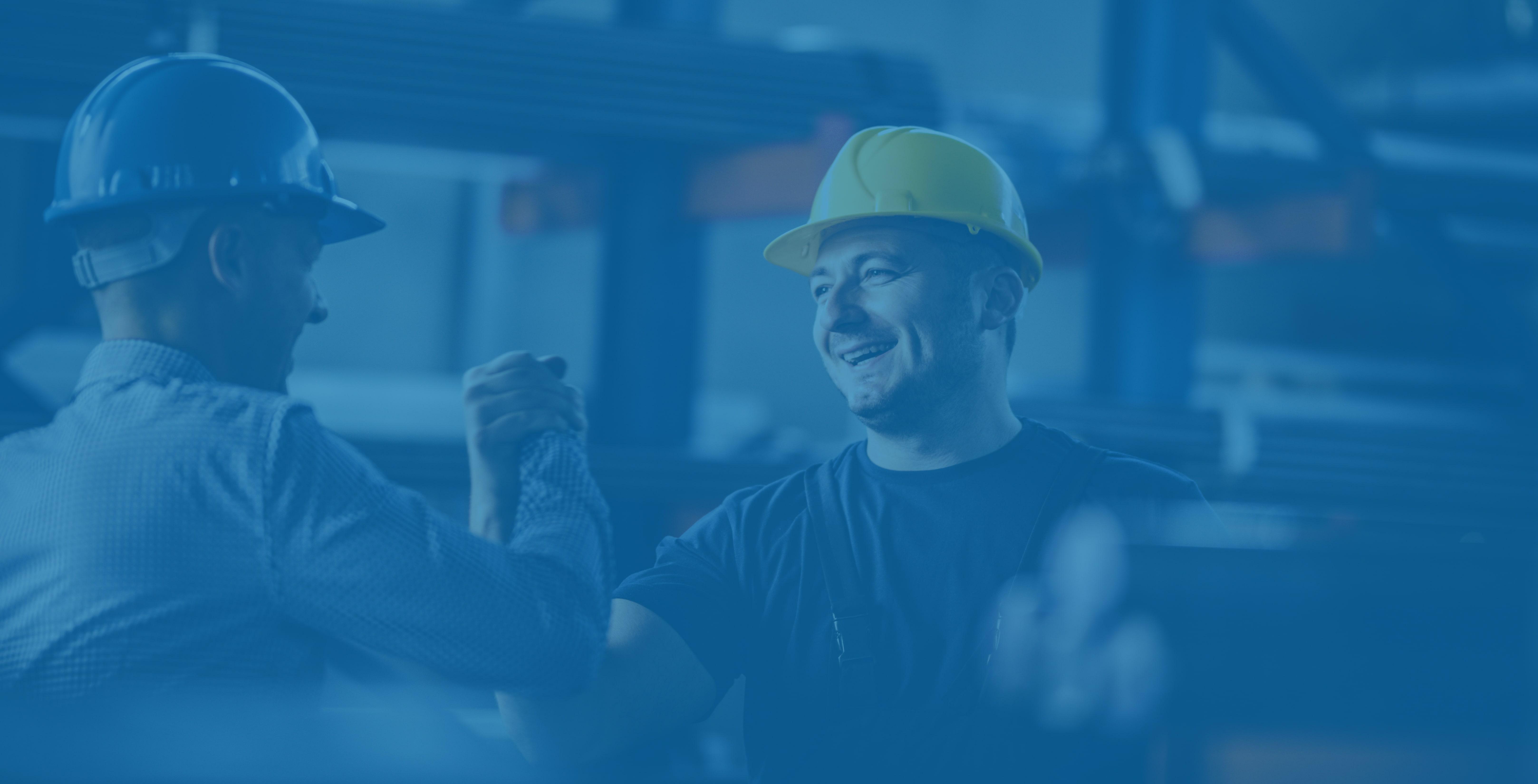 Zwei männliche Lagerarbeiter mittleren Alters in Schutzhelmen reichen sich die Hände und lächeln zur Feier eines gelungenen Jobs.