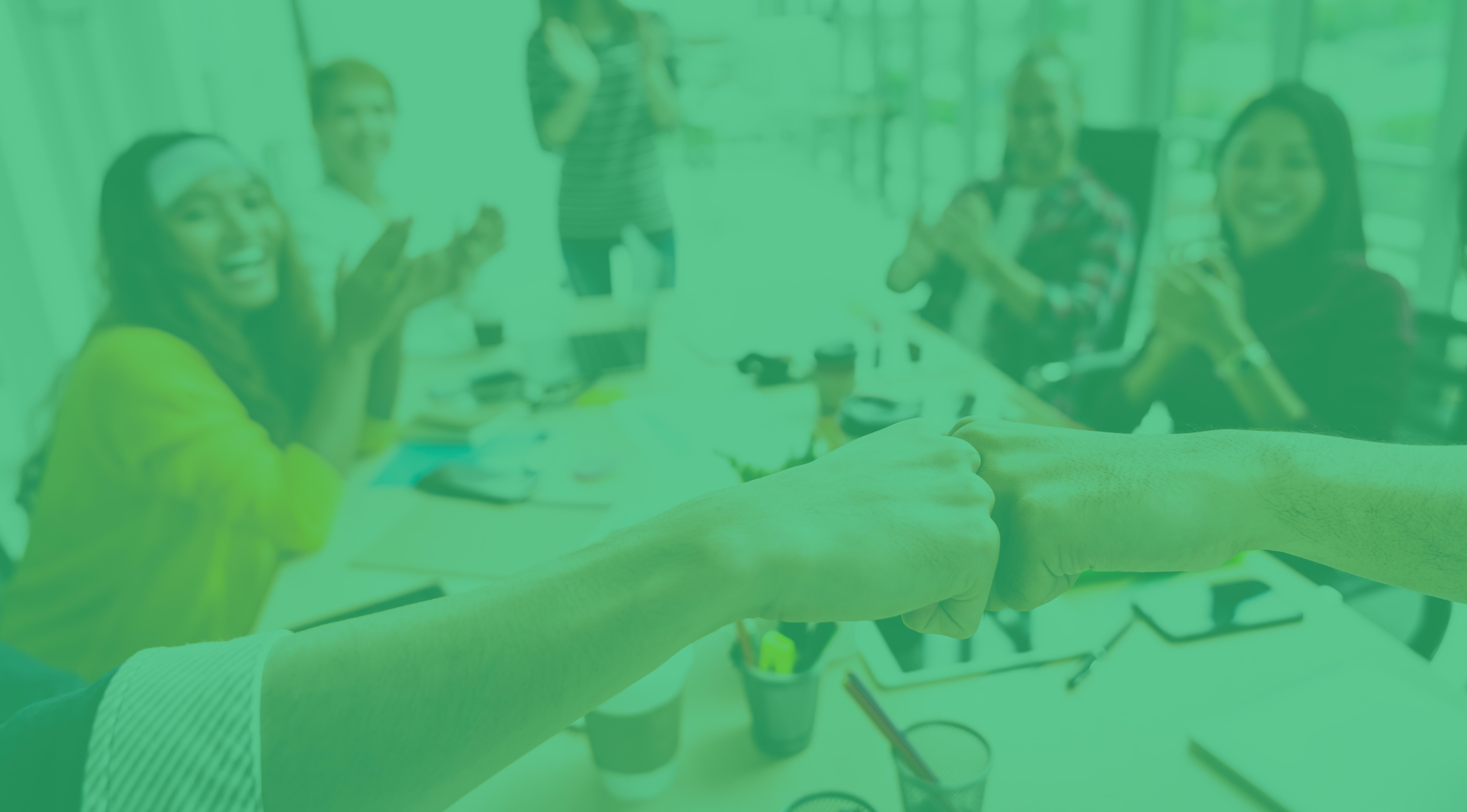 An einem langen Konferenztisch stoßen zwei Personen mit der Faust an, während vier junge Mitarbeiter klatschen und lächeln.