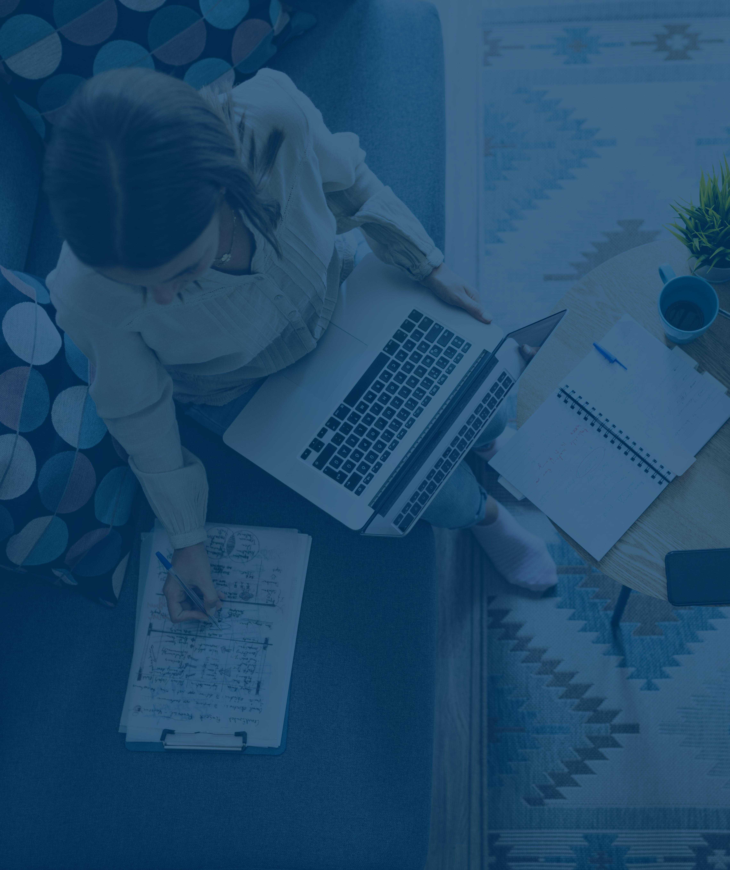 Draufsicht auf eine Frau in einer weißen Bluse, die von zu Hause aus mit ihrem Laptop auf dem Schoß arbeitet, während sie handschriftliche Notizen macht.