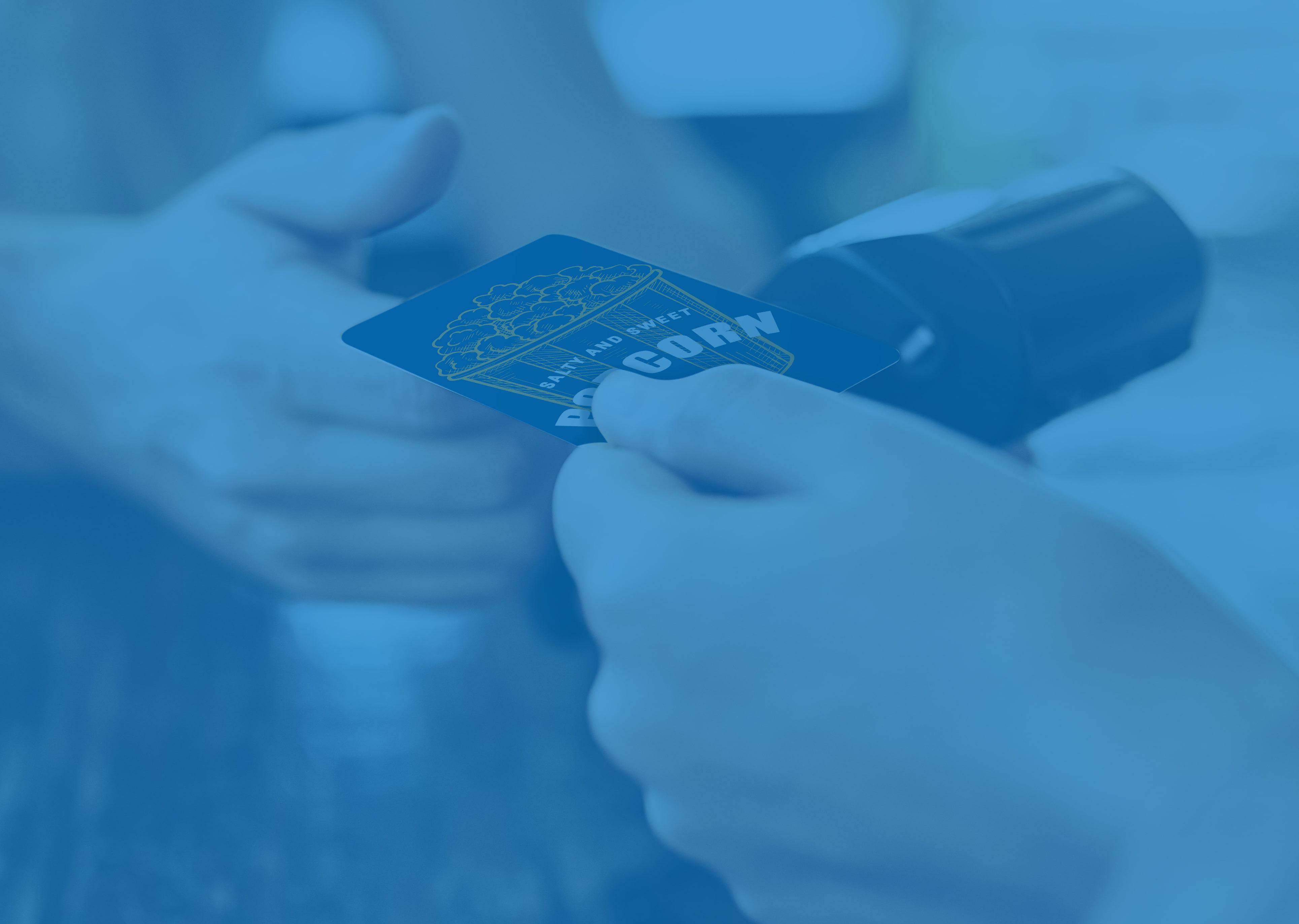 """Nahaufnahme einer Hand, die eine Geschenkkarte zum Bezahlen von Kino-Snacks anbietet, mit einer Geschenkkarte, auf der """"Popcorn"""" steht."""