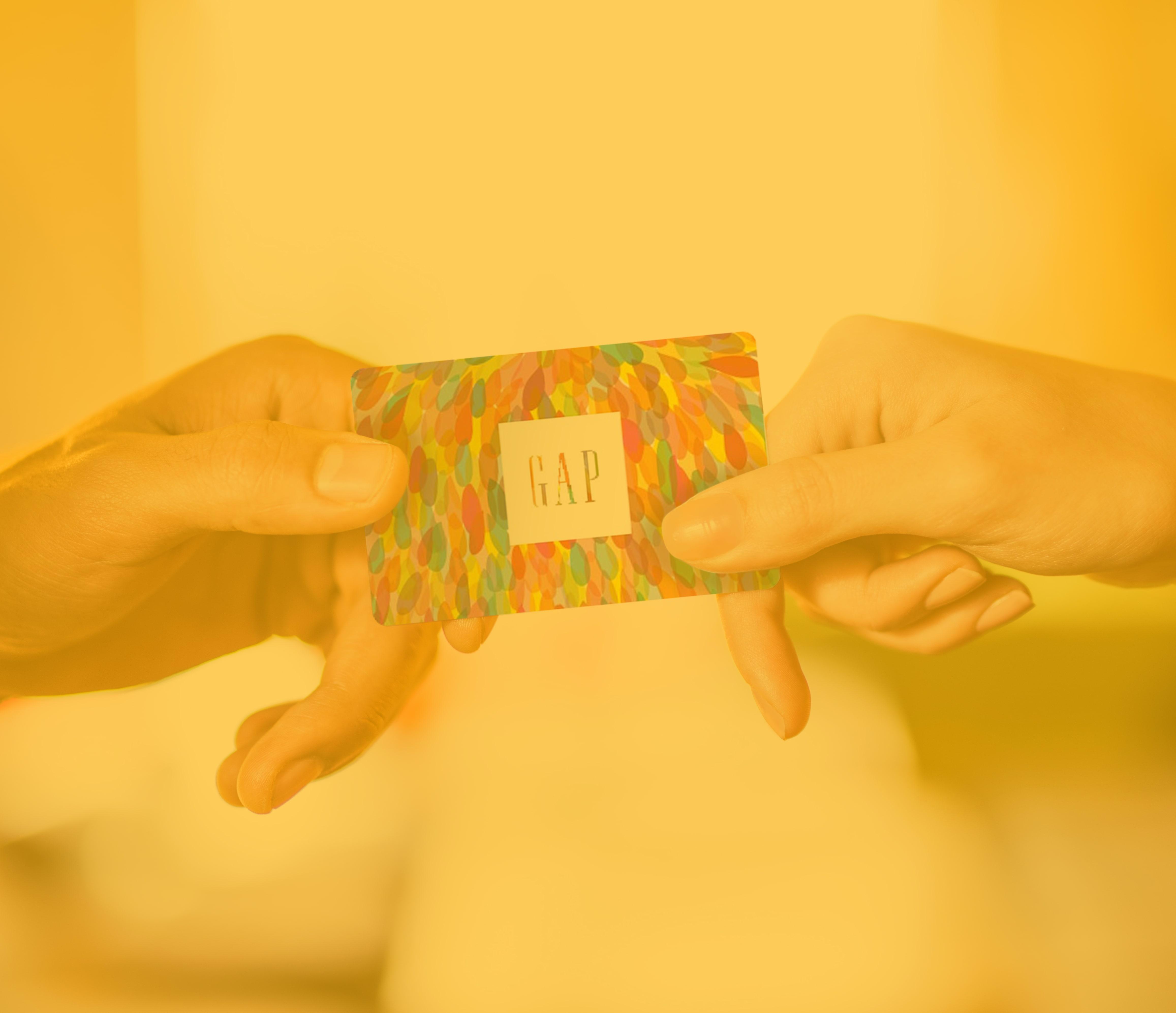 Nahaufnahme der Hand eines Managers, der einer Mitarbeiterin eine Gap-Geschenkkarte als Belohnung für das Erreichen eines Geschäftsziels überreicht.