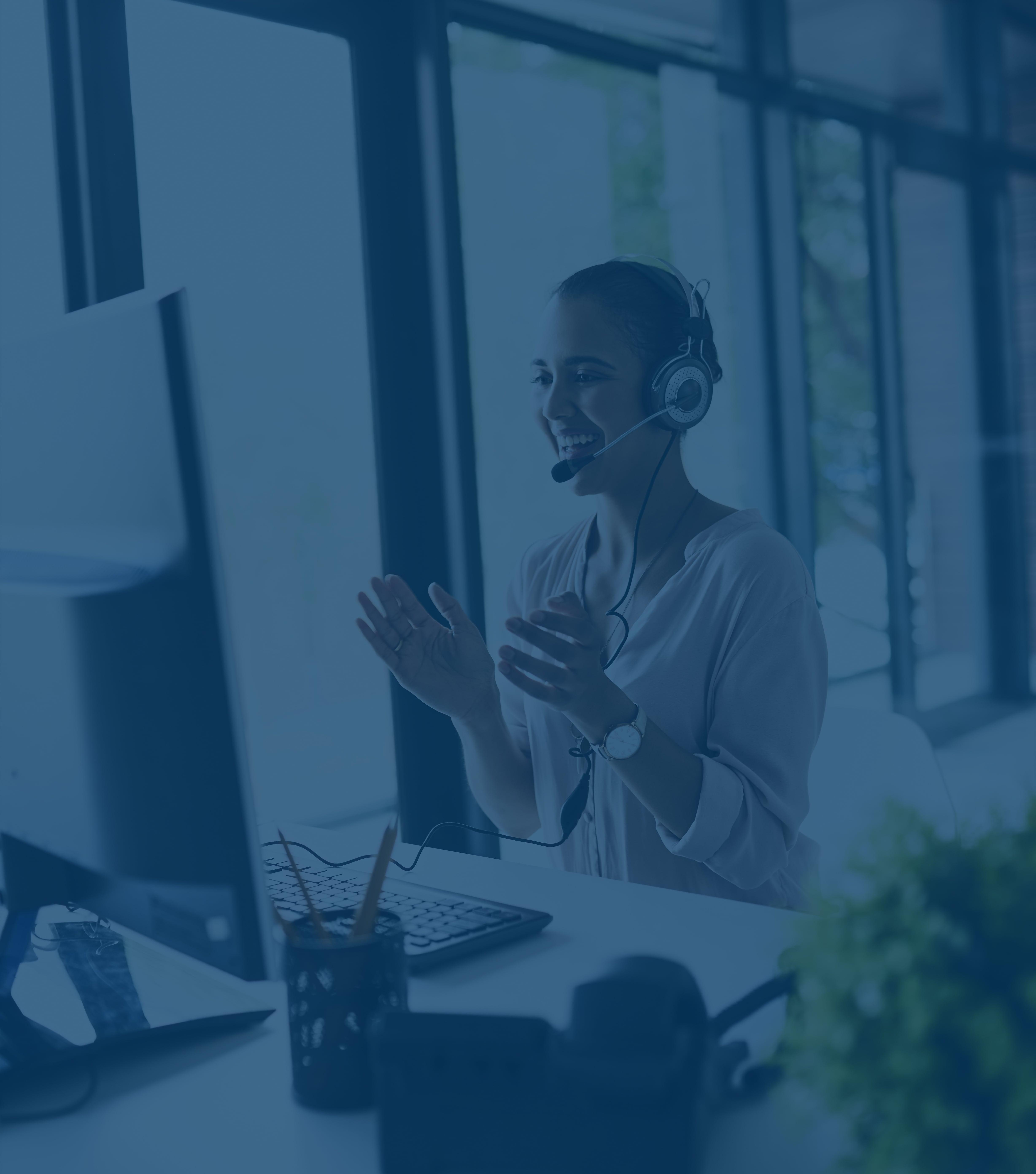 Eine junge Frau mit einem Telefon-Headset sitzt an ihrem Computerbildschirm vor einer Flachglasscheibe. Sie lächelt und klatscht, als sie sich über einen Verkauf freut.