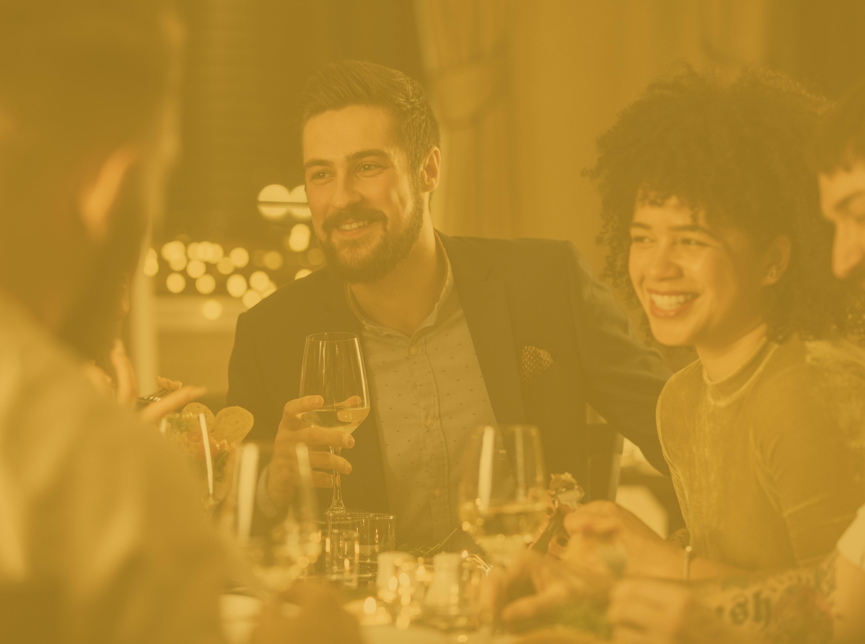 Konzentrieren Sie sich auf einen Mann und eine Frau, die mit einer Gruppe von Freunden ein feines Essen genießen, dank eines Geschenkkartenanreizes, den sie für das Übertreffen ihrer Verkaufsziele erhalten hat.