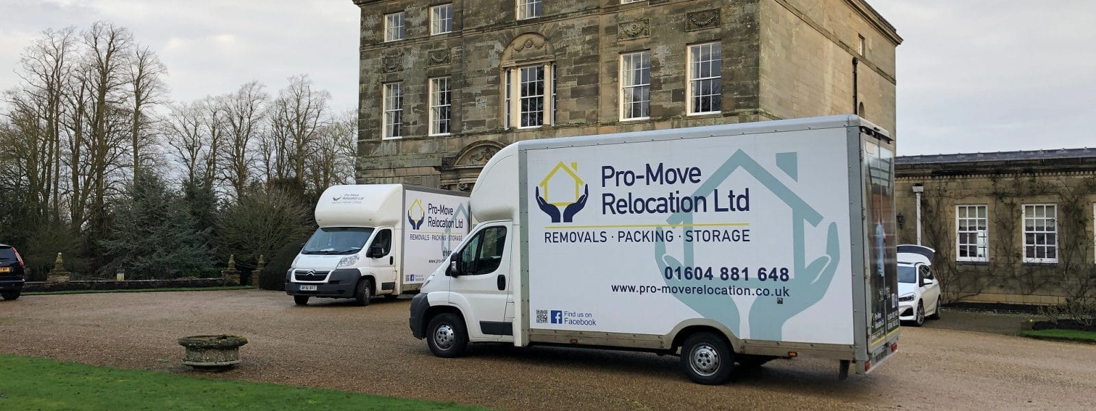 Two Pro Move relocation vans outside a stately home
