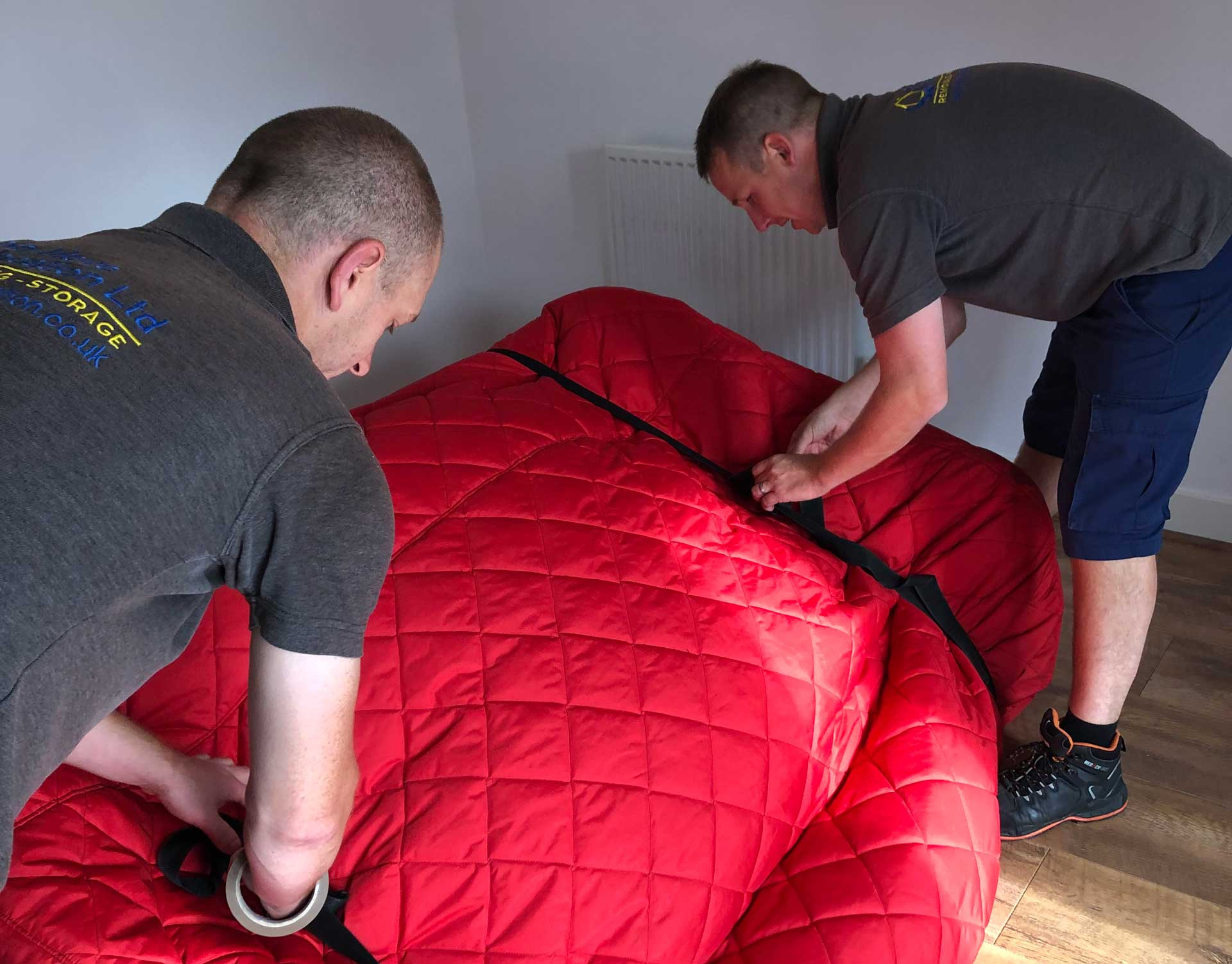 Nick and teammate carefully pad-wrapping a sofa