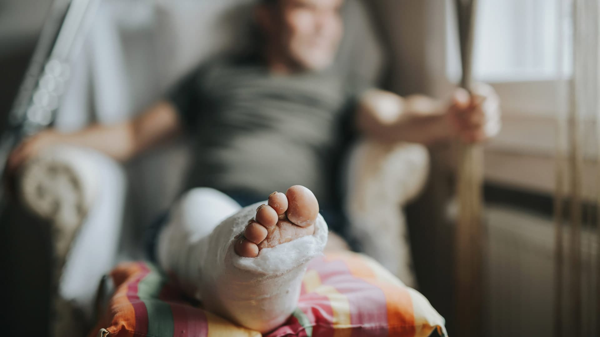 Man with broken leg sitting at home