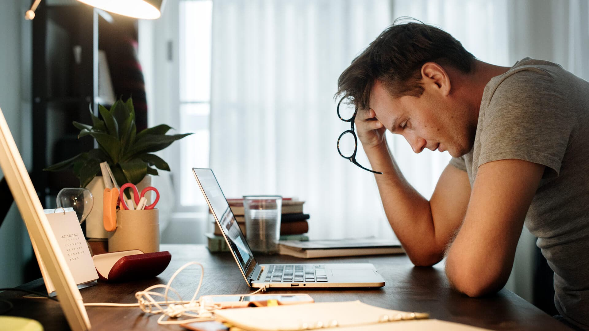 Man stressed while working on laptop at home.