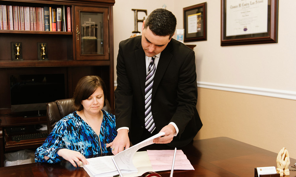 Chris Faucheux reviewing paperwork with co-worker