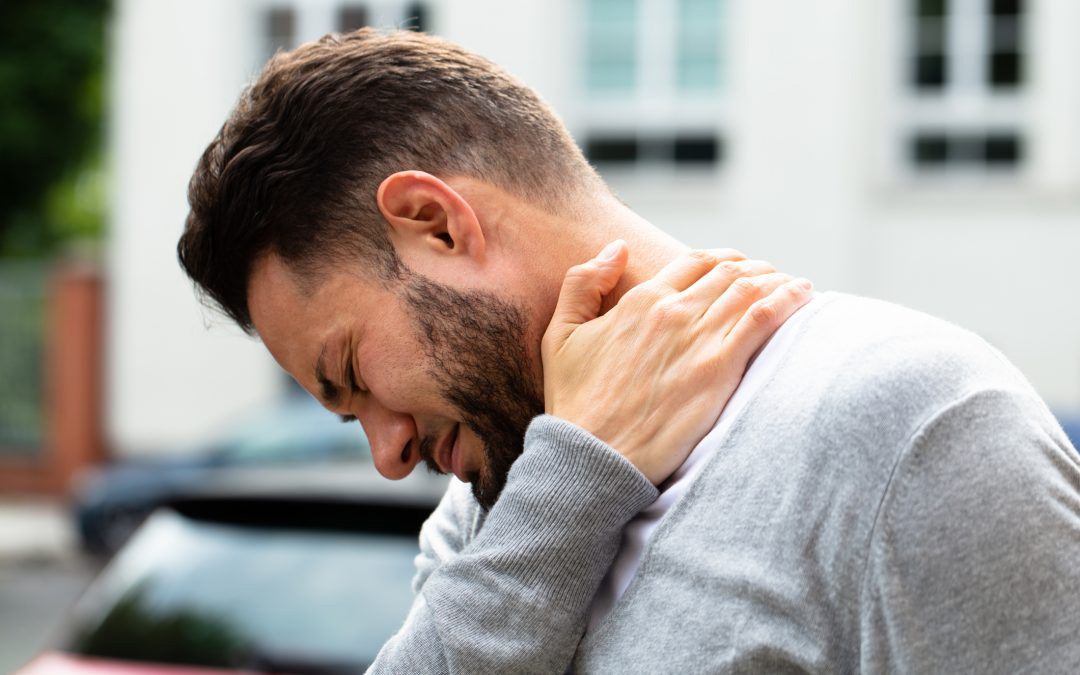 Man holding neck and shoulder in pain.