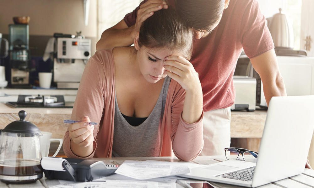 Stressed couple sitting at table reviewing hospital bills