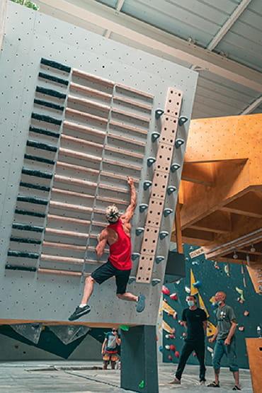 Salle boulderline, homme grimpant barres