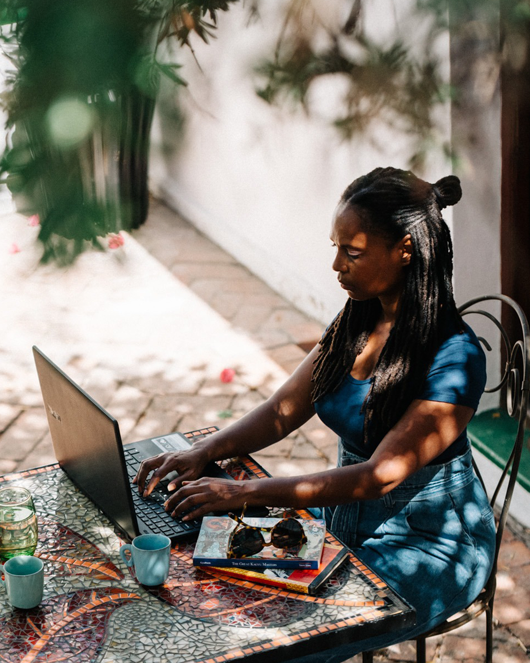 A woman working on her laptop in the garden at Villa Viva.