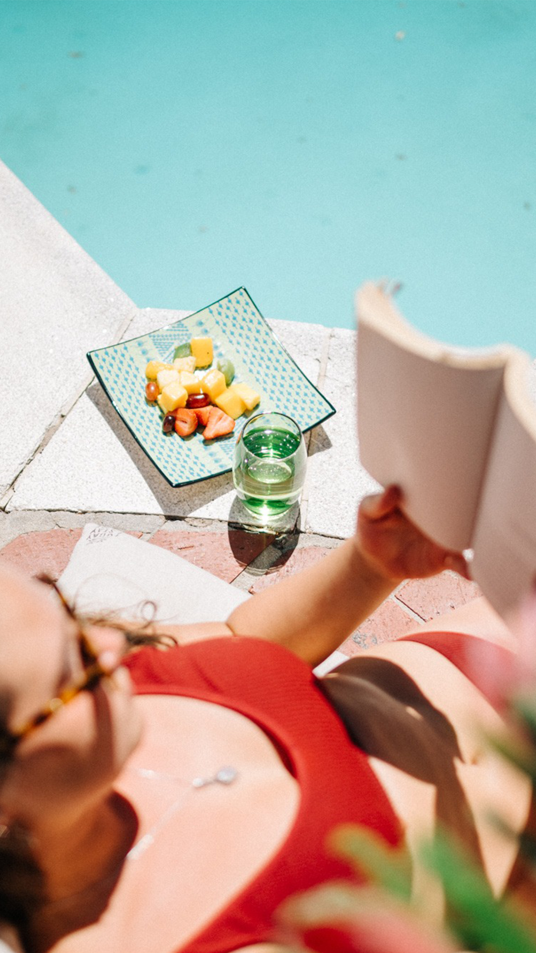A woman reading a book by the pool at Villa Viva.