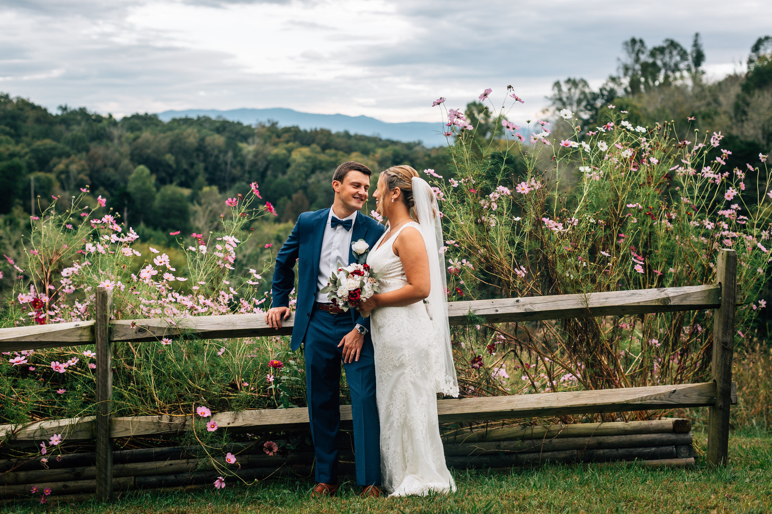 a couple near a fence with flowers on it at flower mountains wedding venue in gatlinburg tennessee after eloping