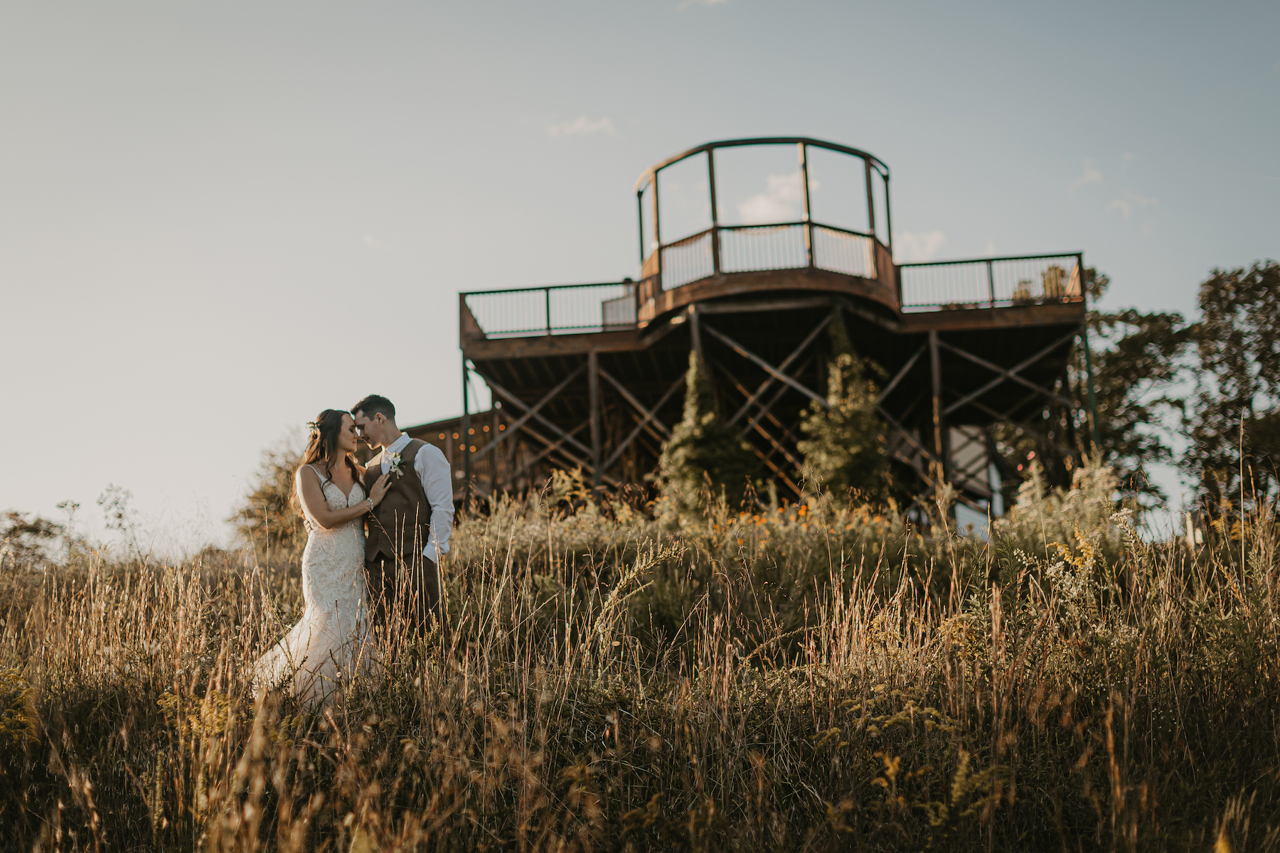A couple in a field with the venue in the background at flower mountain wedding venues in gatlinburg tennessee