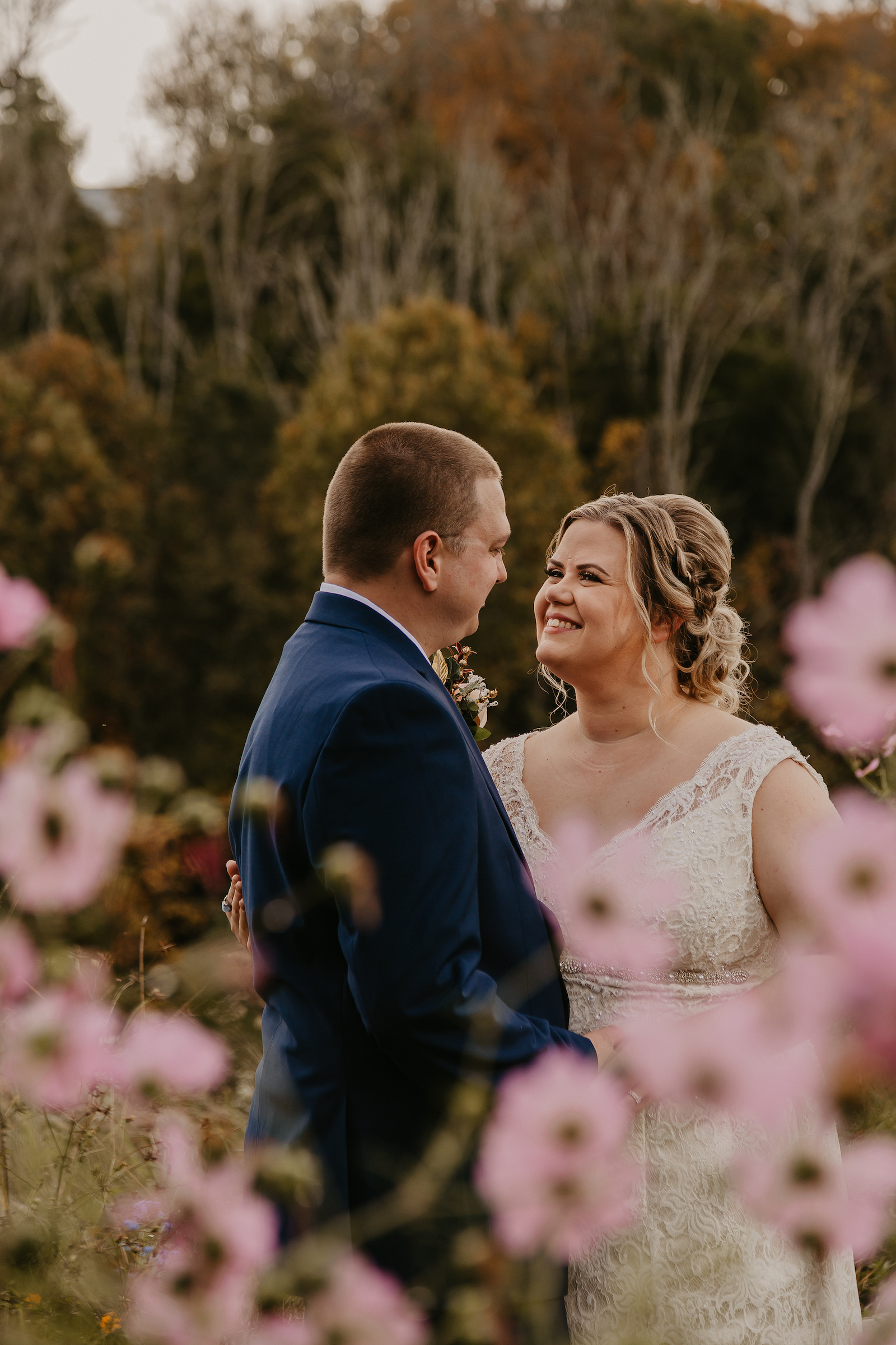 A couple in a field surrounded by flowers at flower mountain wedding venues in gatlinburg tennessee