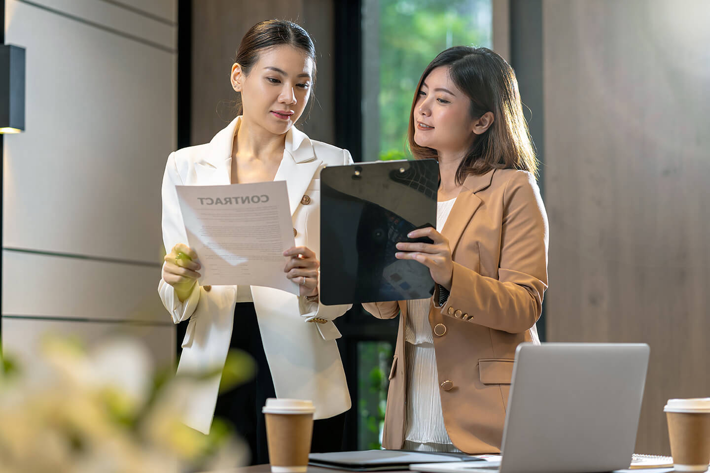 Two asian businesswomen discussing with the partner business about business contract by technology laptop in modern meeting room, office or working space, coffee break, partner and colleague concept
