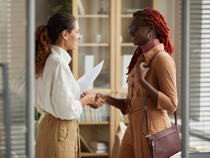 Two young women shaking hands at job interview