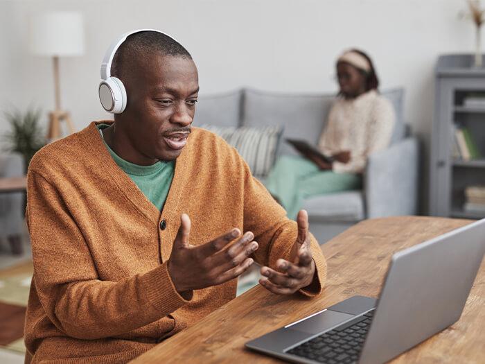 African American man in online meeting speaking wearing a headset