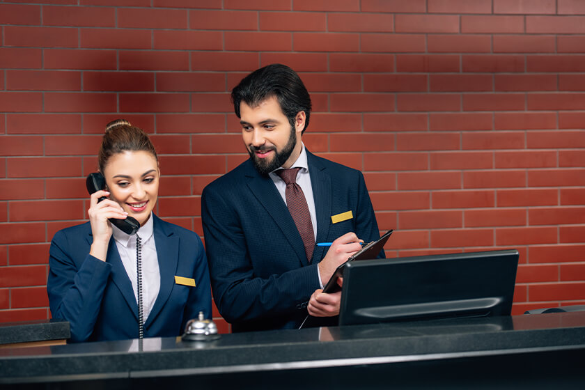 Happy young hotel receptionists at workplace