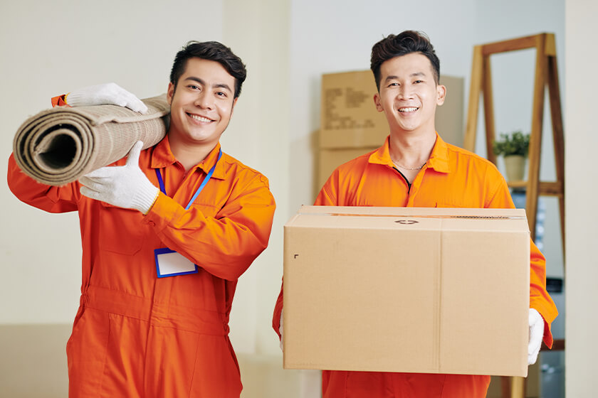 Movers carrying carpet and cardboard box