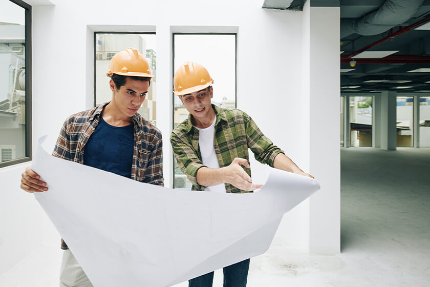 Two workers with construction plan