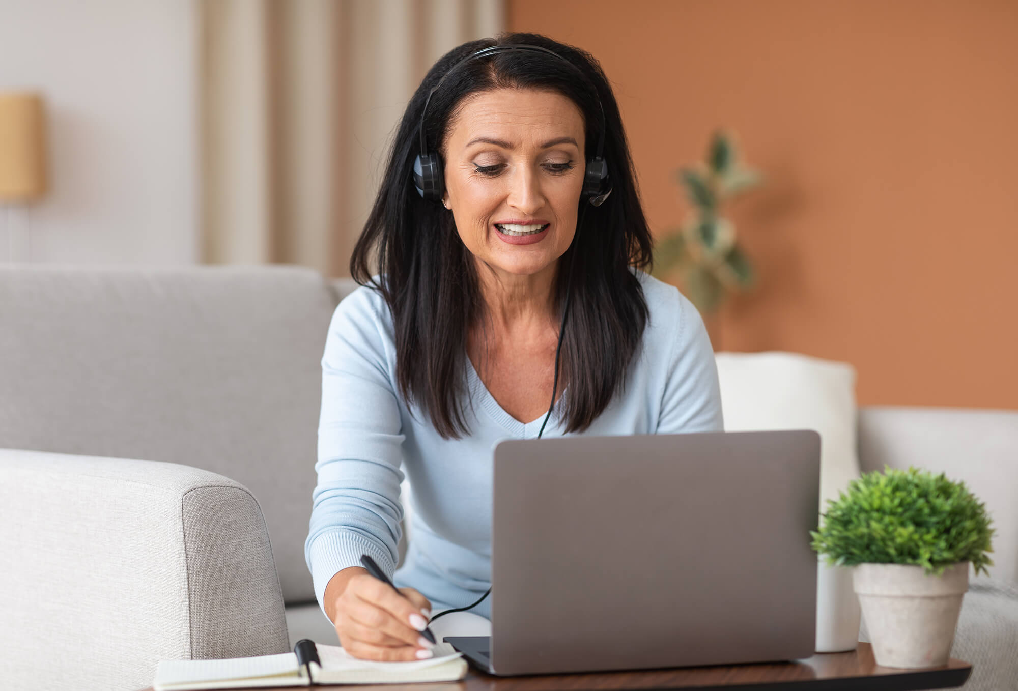 Mature woman on headset writing and using laptop at home