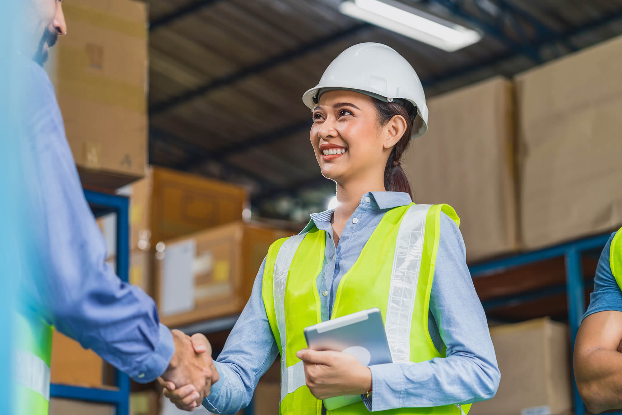 Manager of warehouse worker hand shake with assistant manager woman in local warehouse