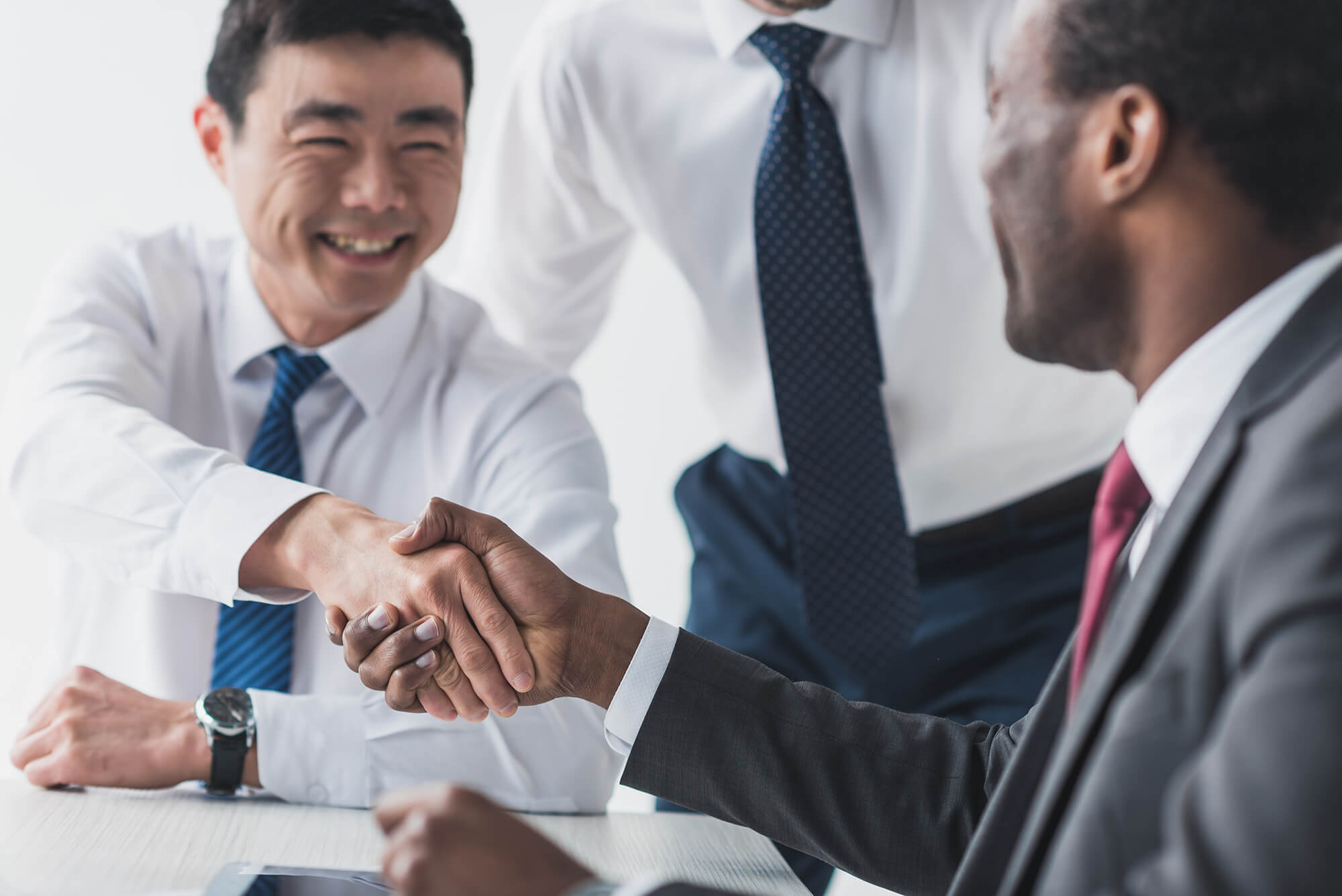 Selective focus of African American and Asian businessmen shaking hands after meeting