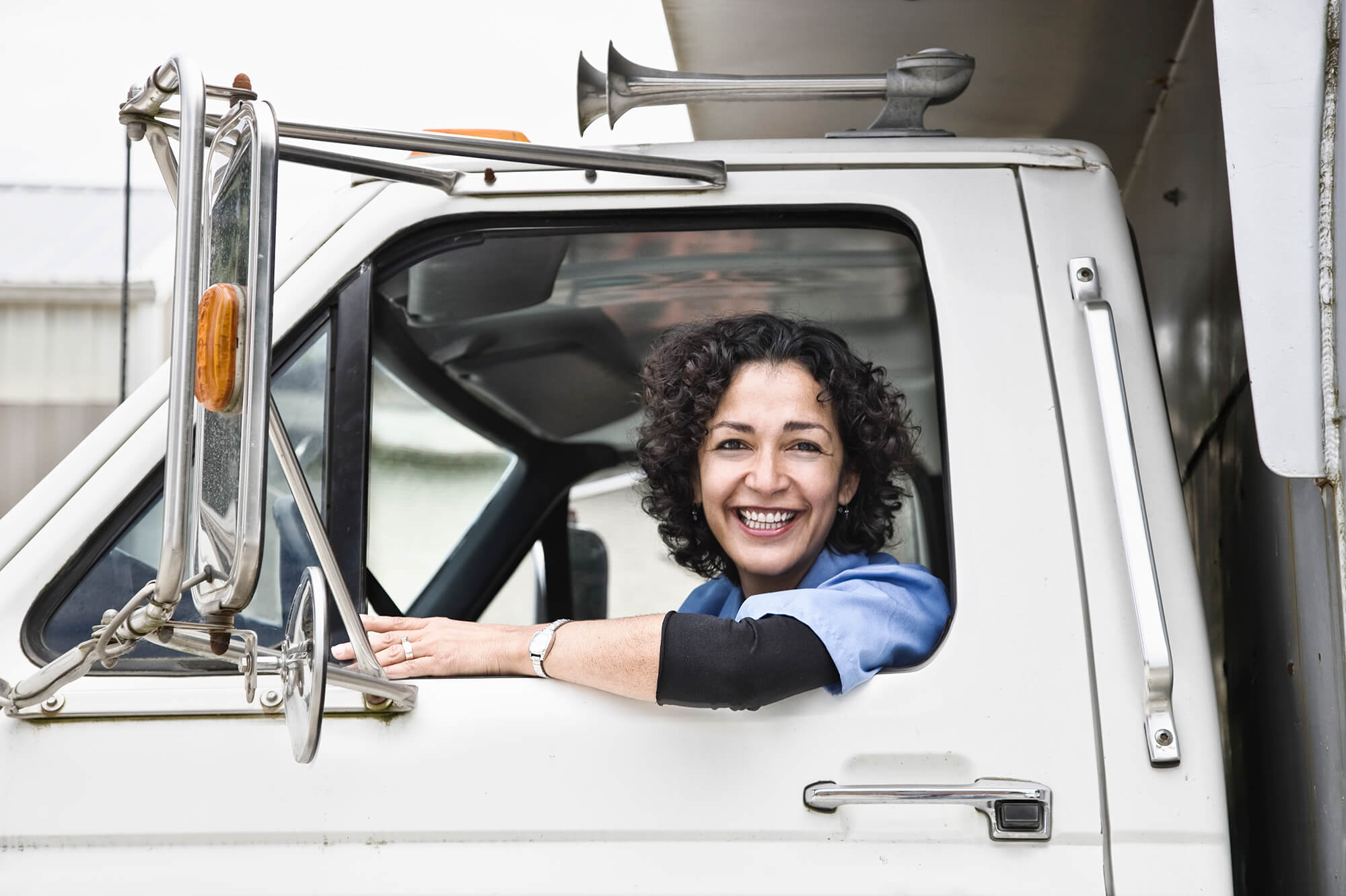 Hispanic woman truck driver and company delivery truck