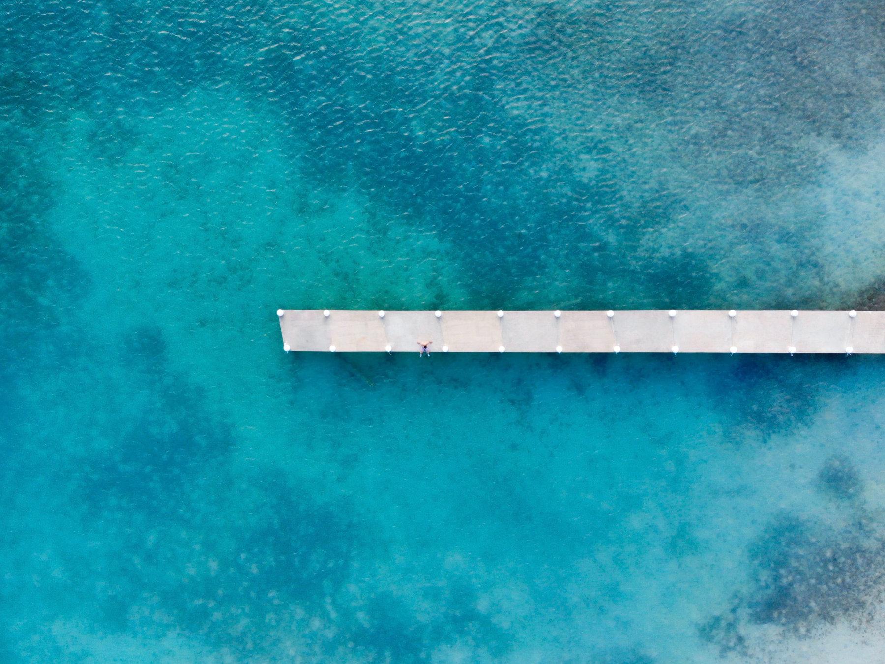 Ein Steg, der ins türkise Meer führt, direkt von oben fotografiert.