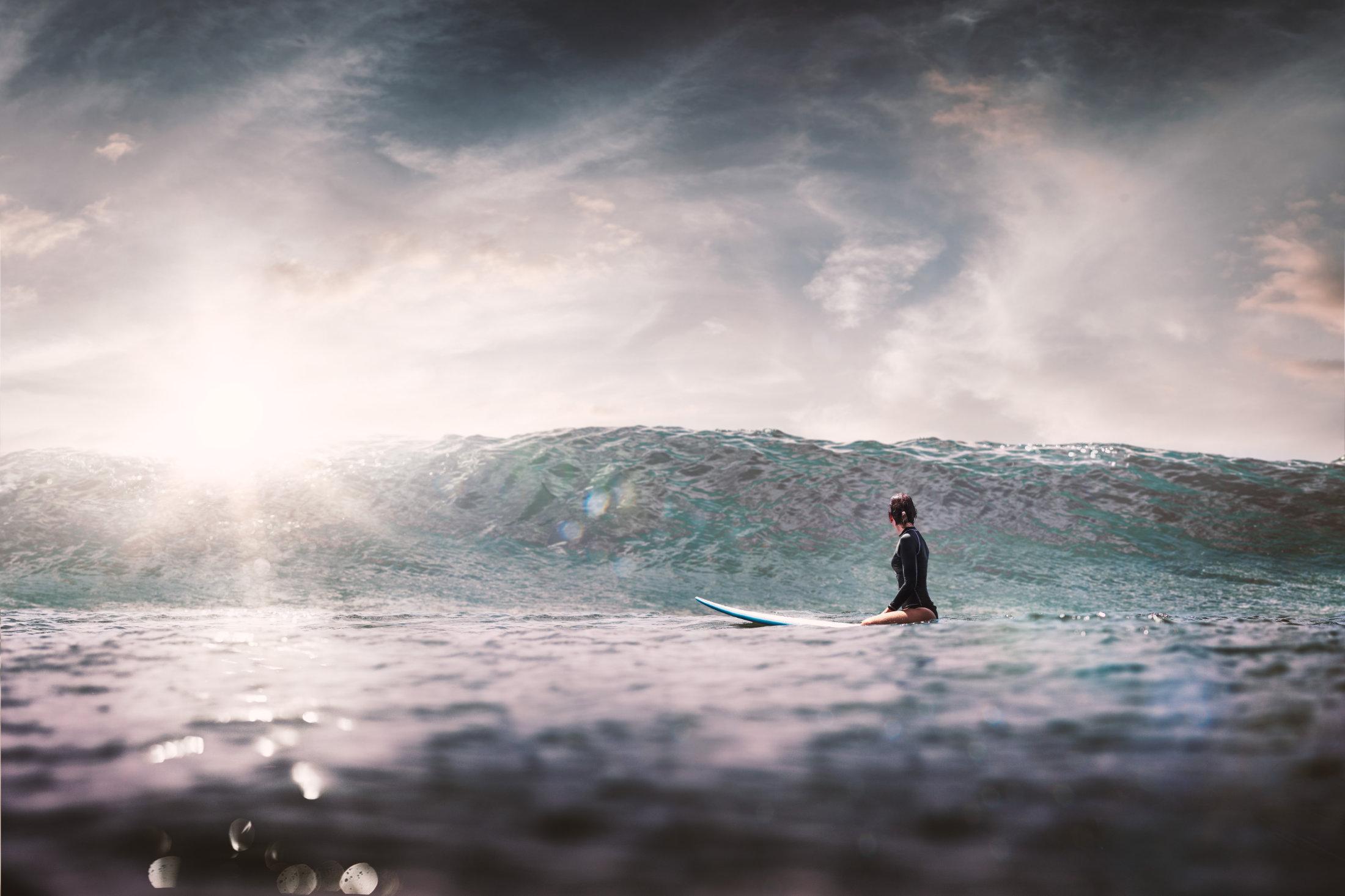 Frau sitzend auf einem Surfbrett,  hinausblickend aufs Meer auf eine herannahende Welle.