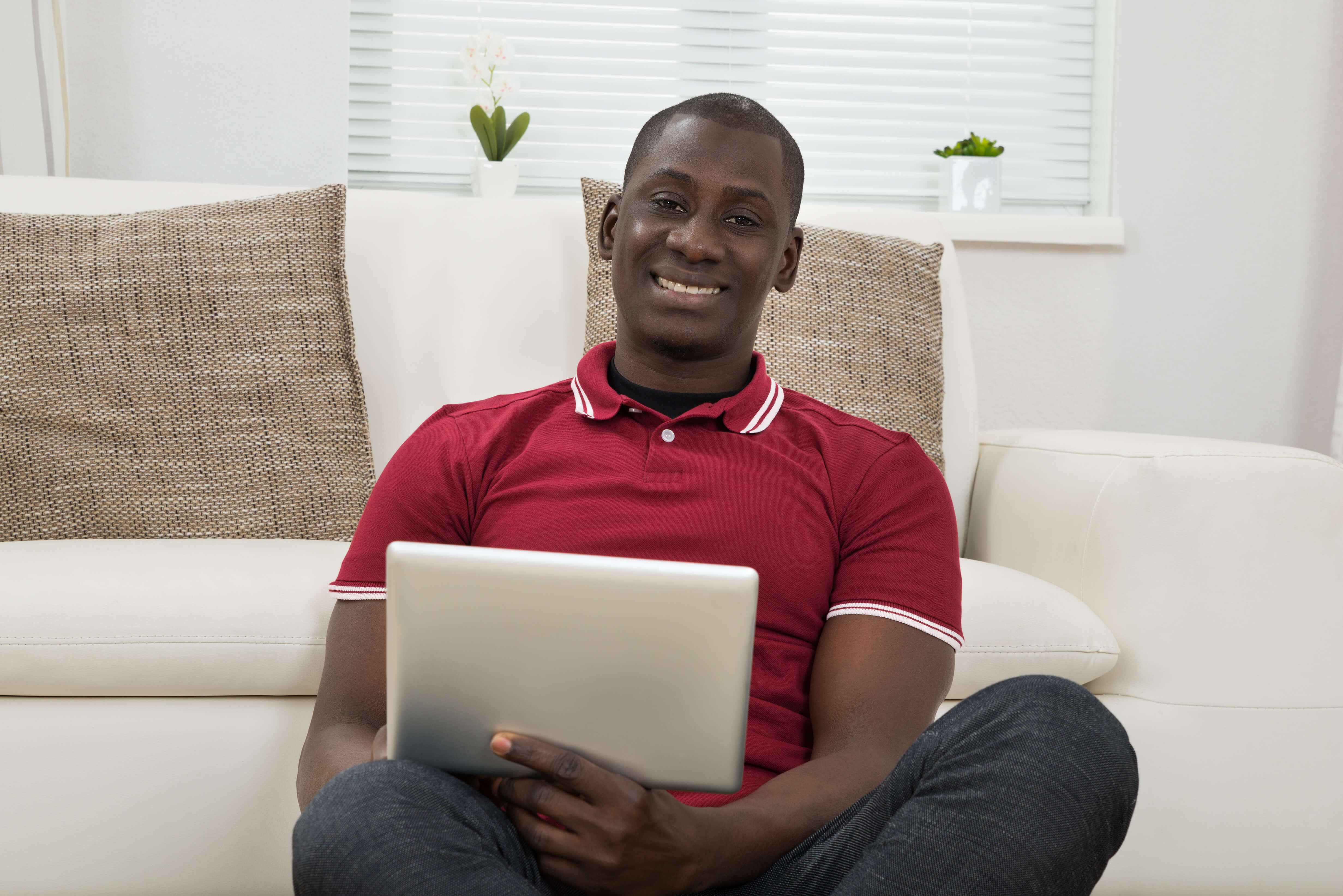 Man sitting comfortably on the floor holding a tablet to demonstrate the ease of attending a live orientation webinar.