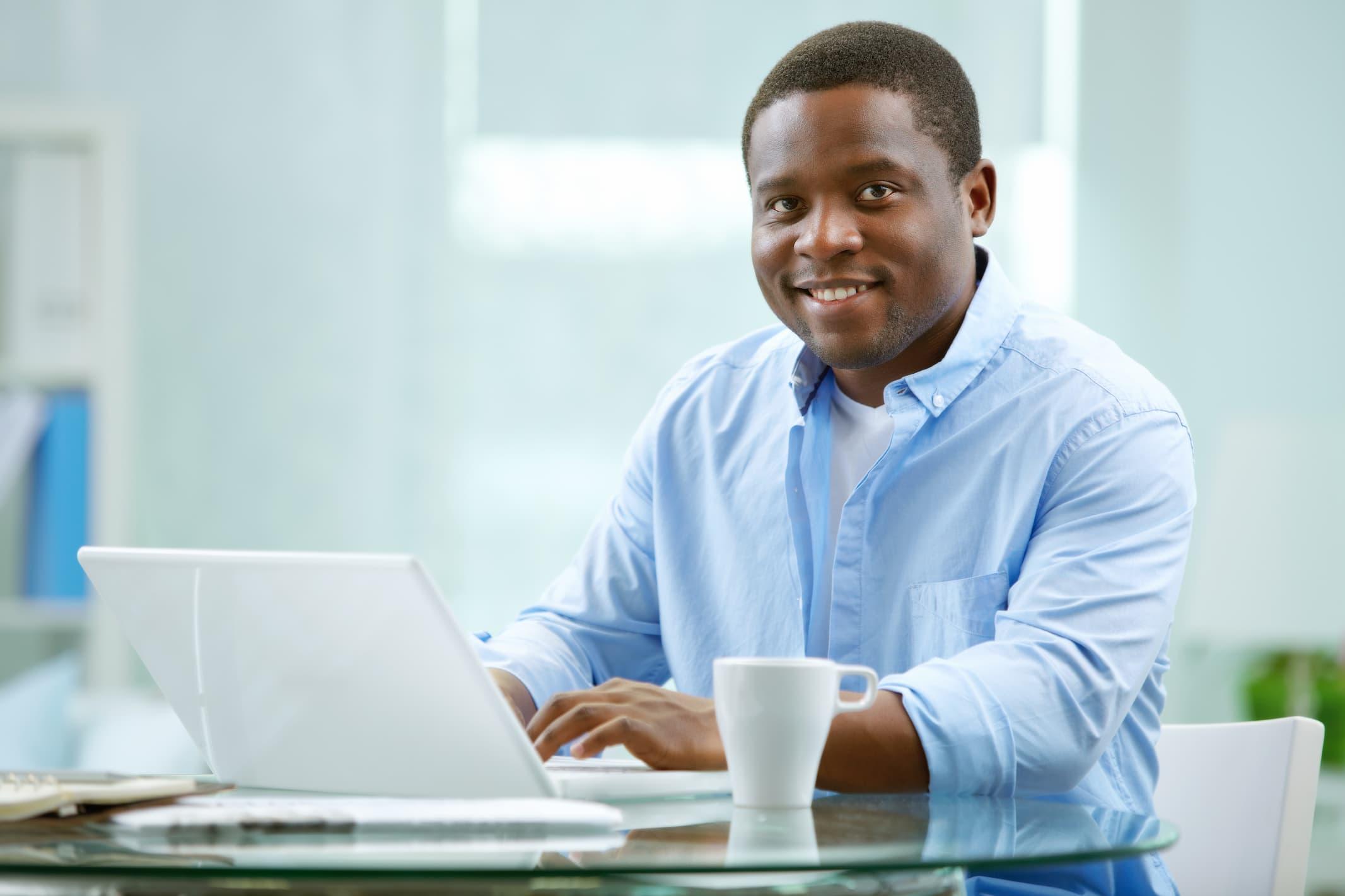 Man sitting at computer smiling