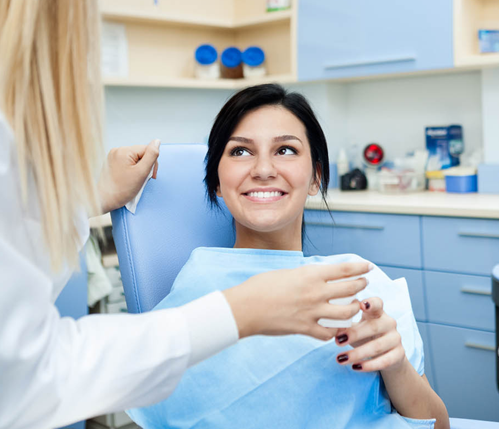 happy patient holding a water cup given by dentist