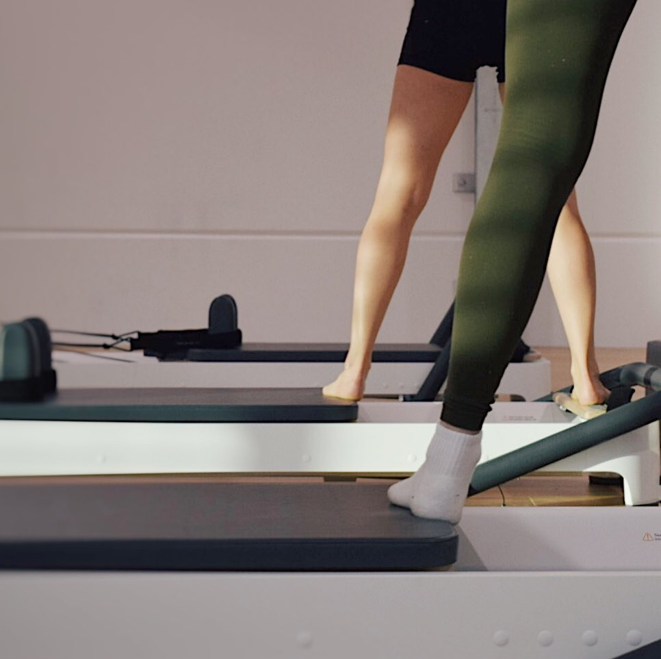 close up of people standing on pilates reformer machines