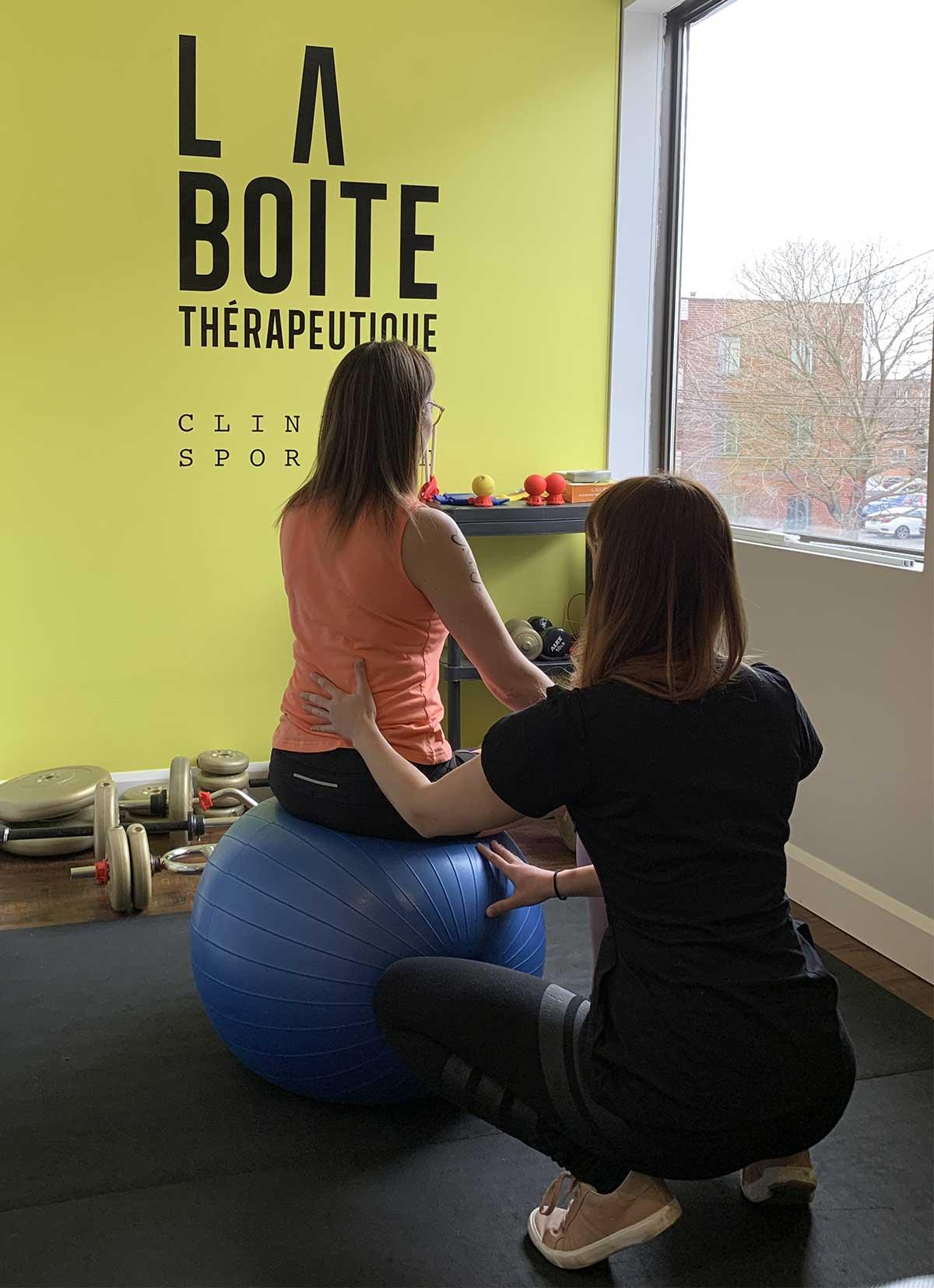 Femme assise sur un ballon d'exercice qui reçoit un traitement chiropratique