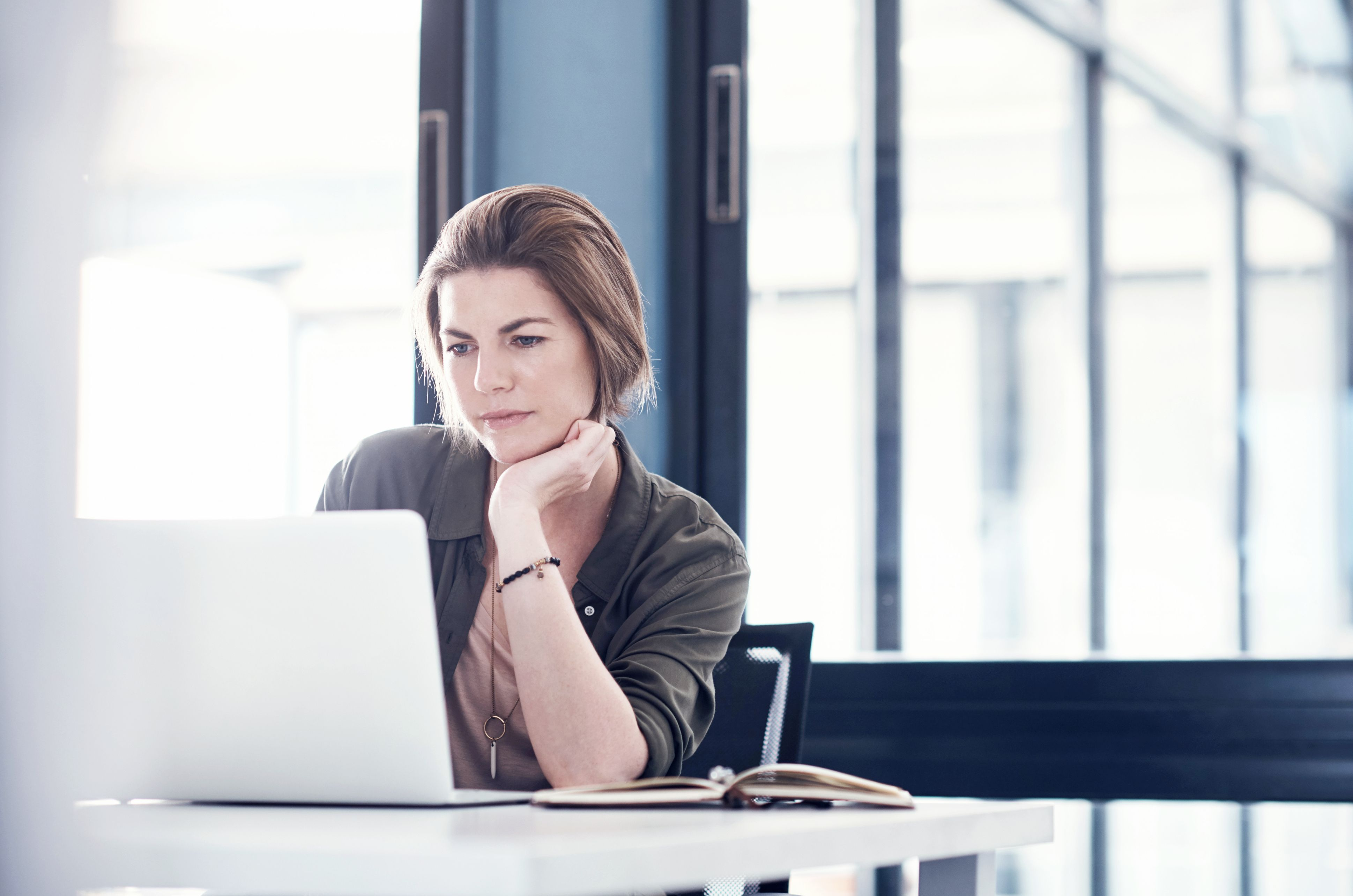 lady looking pensively at her laptop screen in an office