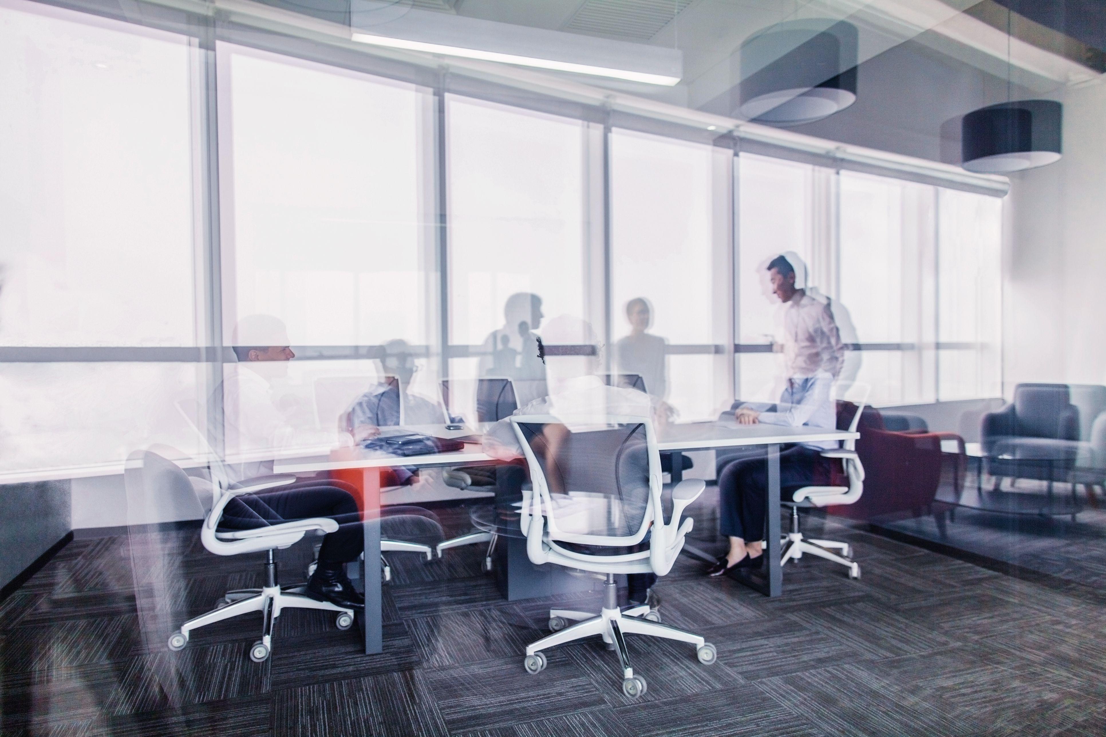 An office set-up with desks and office chairs, with a large glass window in the background