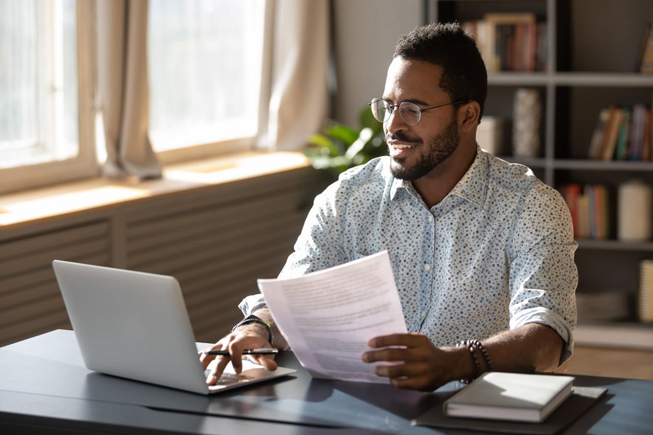 homem usando o computador segurando documento