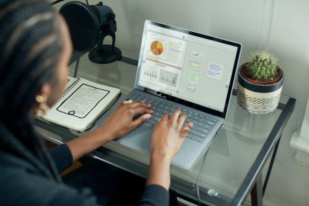 mulher digitando em um computador exibindo graficos