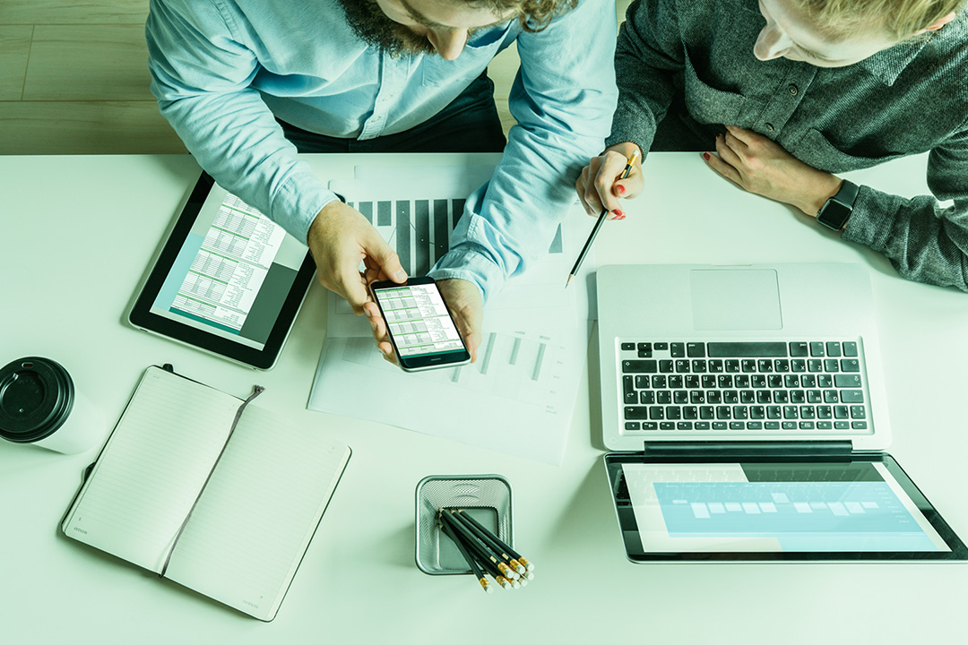 duas pessoas analisando dados em dispositivos eletronicos