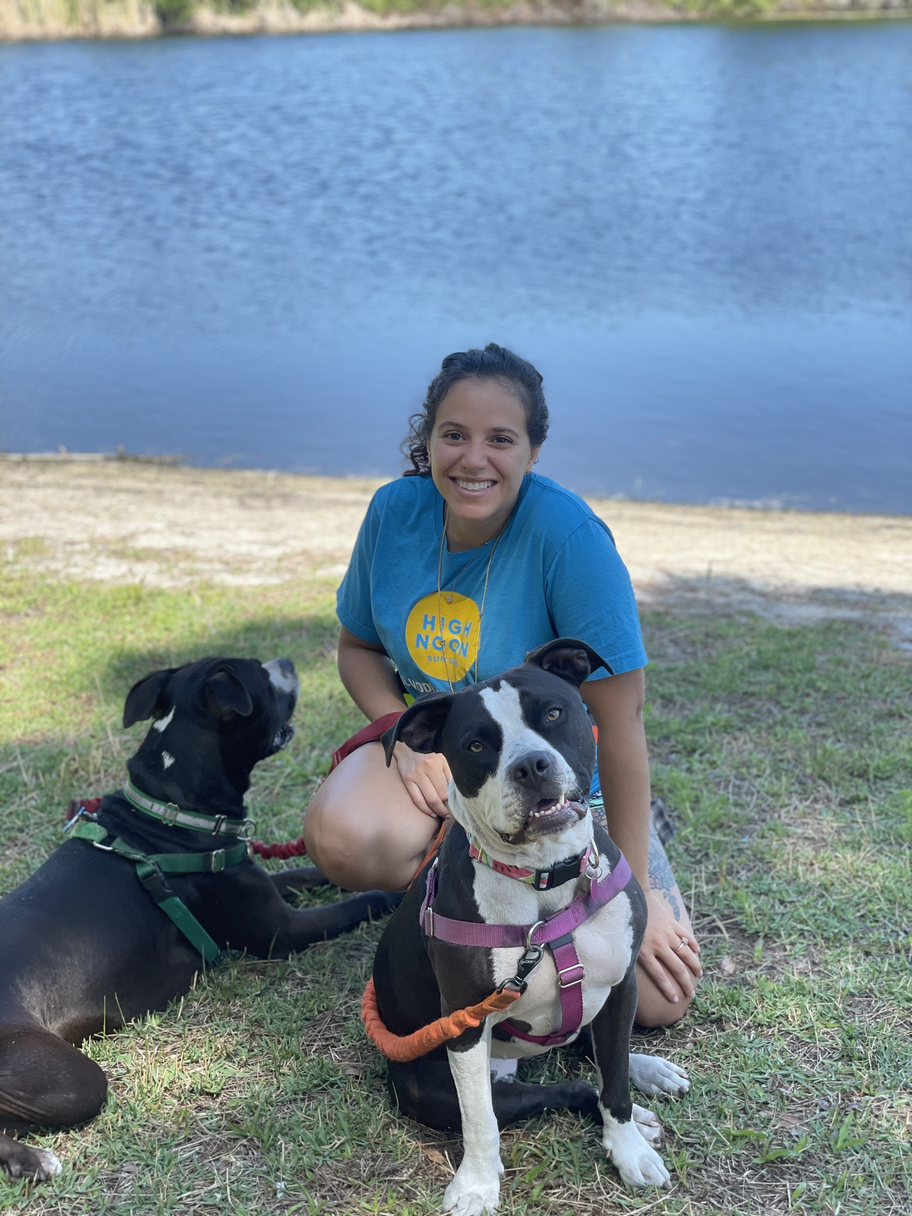 Dog trainer with 2 happy dogs near a lake