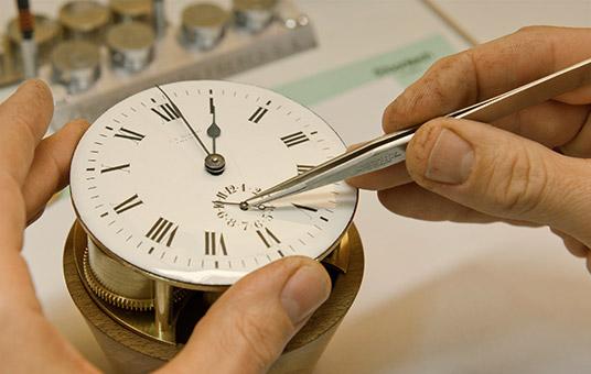 Uhrmacher Florian Dostal restauriert das Ziffernblatt eines historischen Chronometers.