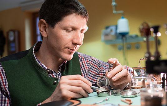 Uhrmacher Florian Dostal repariert eine Uhr