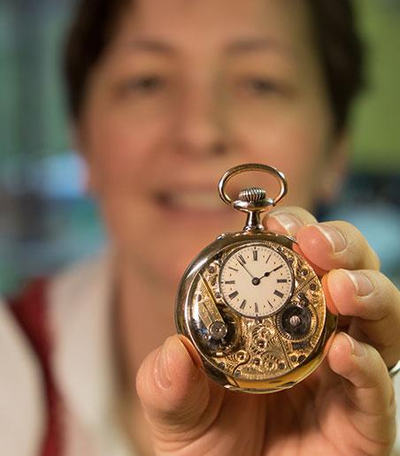 Uhrmacherin Barbara Dostal mit einer historischen goldenen Taschenuhr