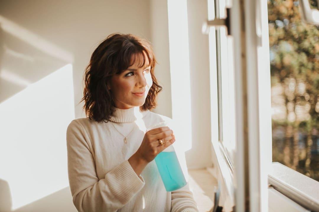 Frau reinigt Fenster mit everdrop Glasreiniger