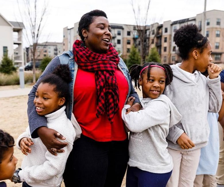 A woman and her daughters laugh while embracing.